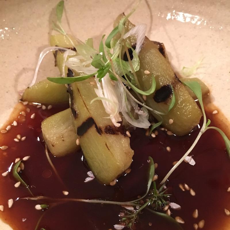 Berenjena yakitori a la brasa con sésamo, aceite de sésamo, reducción de soja y aros de cebolla